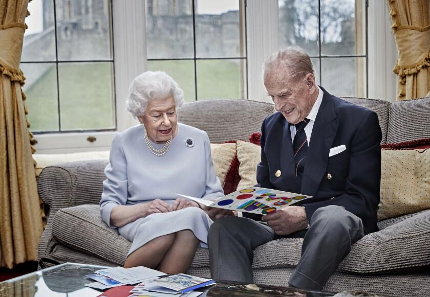 la reina Isabel II y el príncipe Felipe leen una tarjeta de aniversario de parte de sus bisnietos,