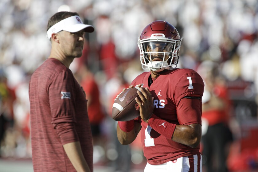 Oklahoma quarterback Jalen Hurts warms up under the watch of coach Lincoln Riley before the game against Houston on Sept. 1, 2019.