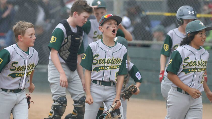 Seaview Little League's Will Stanley, center, cheers after his team defeats Costa Mesa American in a
