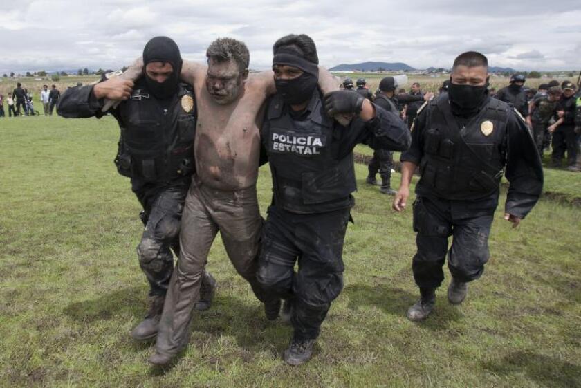 Agentes estatales caminan el viernes 13 de agosto de 2010, con uno de los cinco presuntos asaltantes que fueron linchados por pobladores de la comunidad de Tlachaloya, en el estado de México (México).EFE/Mario Vázquez/MVT/Archivo