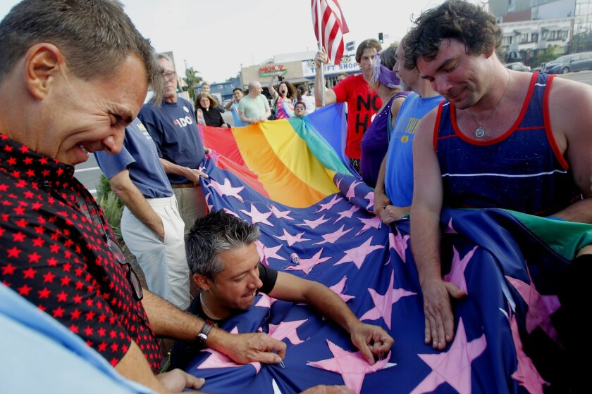 The final pink stars are sewn on the Pride Constellation flag before being raised as people celebrate the U.S. Supreme Court's ruling on marriage equality, making same-sex marriage legal in all 50 states, in the Hillcrest community of San Diego on Friday.