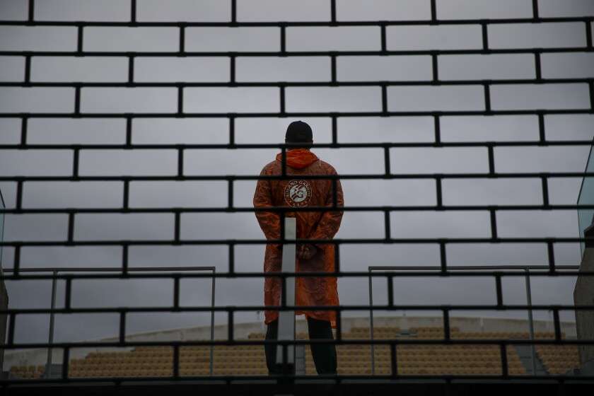 A stadium employee looks out over empty seats during first round matches of the French Open tennis tournament at the Roland Garros stadium in Paris, France, Sunday, Sept. 27, 2020. (AP Photo/Christophe Ena)