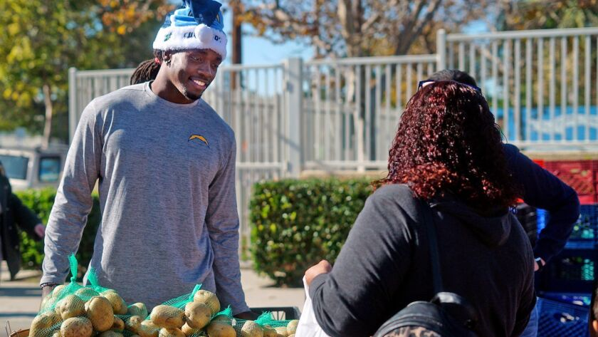 Los Angeles Chargers running back Melvin Gordon passes out produce during an event for his new found