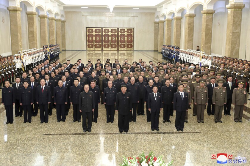 """In this photo provided by the North Korean government, North Korean leader Kim Jong Un, center front, stands with Politburo members and other senior officials in entrance hall of the Kumsusan Palace of the Sun in Pyongyang, North Korea, Thursday, July 8, 2021. Kim made a just-after-midnight appearance together with an entourage of top officials, to pay his respects to North Korea's past leader Kim Il Sung at a giant palace on the outskirts of Pyongyang. Independent journalists were not given access to cover the event depicted in this image distributed by the North Korean government. The content of this image is as provided and cannot be independently verified. Korean language watermark on image as provided by source reads: """"KCNA"""" which is the abbreviation for Korean Central News Agency. (Korean Central News Agency/Korea News Service via AP)"""