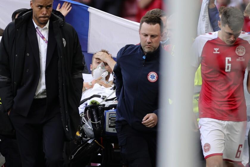 Paramédicos retiran en camilla al jugador danés Christian Eriksen, quien se desvaneció en un partido