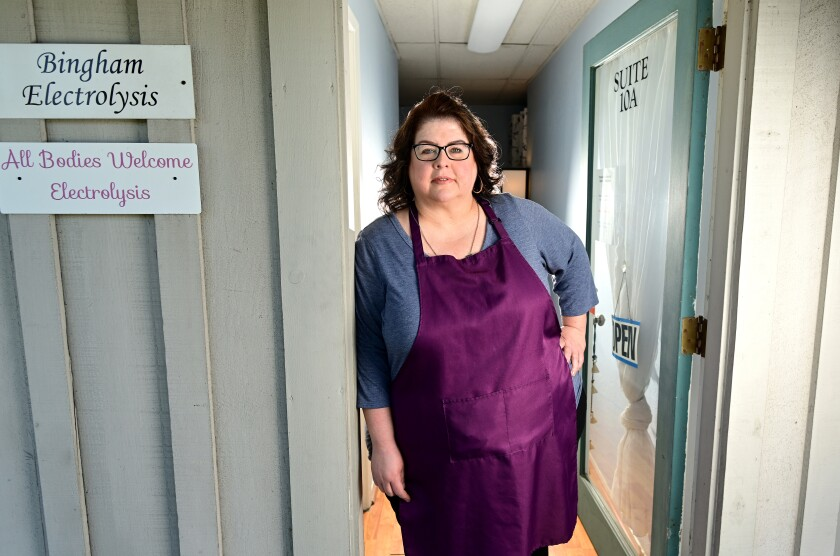 A woman stands in the doorway of her office.