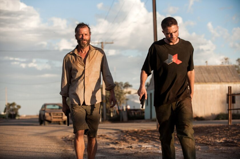 """This image released by A24 Films shows Guy Pearce, left, and Robert Pattinson in a scene from """"The Rover."""" (AP Photo/A24 Films, Matt Nettheim)"""
