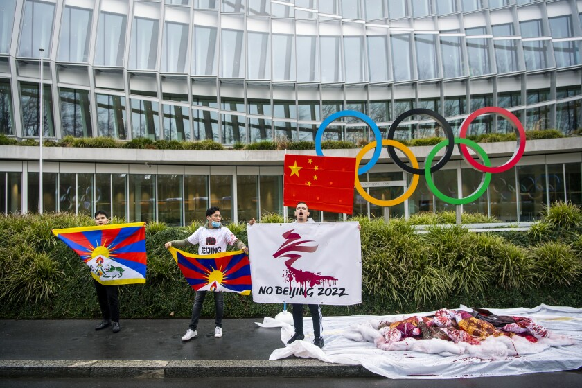 """Protesters hold Tibetan flags during a protest against Beijing 2022 Winter Olympics by activists of the Tibetan Youth Association in Europe, in front of the International Olympic Committee, IOC, headquarters in Lausanne, Switzerland, Wednesday, Feb. 3, 2021. A coalition of 180 rights groups is calling for a boycott of next year's Beijing Winter Olympics tied to reported human rights abuses in China. The games are to open on February 4, 2022. The coalition is made up of groups representing Tibetans, Uighurs, Inner Mongolians and others. The group has issued an open letter to governments calling for a boycott of the Olympics """"to ensure they are not used to embolden the Chinese government's appalling rights abuses and crackdowns on dissent."""" (Jean-Christophe Bott/Keystone via AP)"""