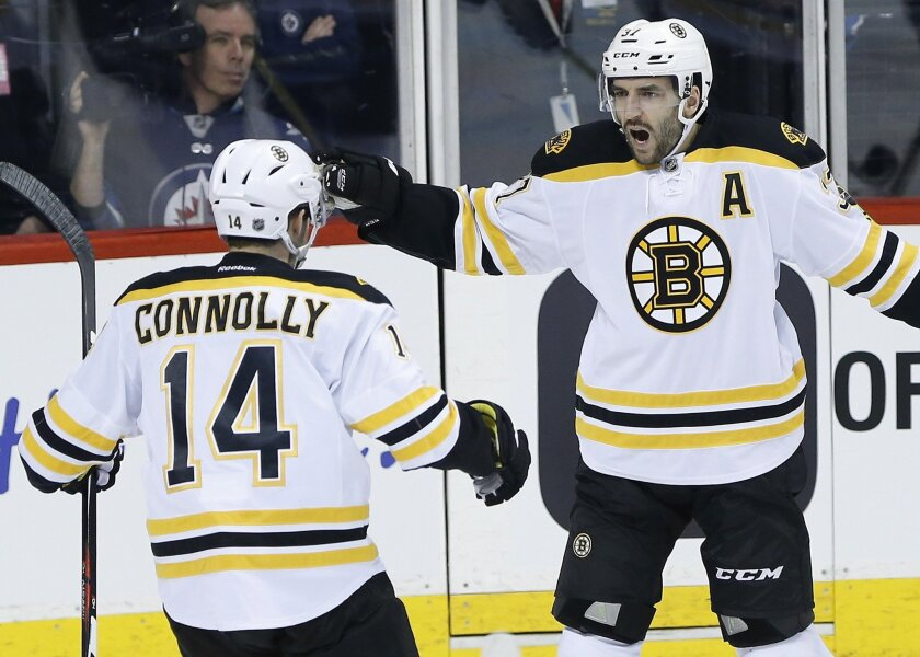 Boston Bruins' Brett Connolly (14) and Patrice Bergeron (37) celebrate Bergeron's goal against the Winnipeg Jets during the first period of an NHL hockey game Thursday, Feb. 11, 2016, in Winnipeg, Manitoba. (John Woods/The Canadian Press via AP)