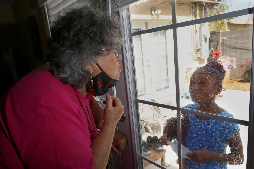 """Zita Robinson, left, who's 77 and diabetic, blows a kiss to her granddaughter Traris """"Trary"""" Robinson-Newman, 8, who blows a kiss back to her, Tuesday, Aug. 4, 2020, in Phoenix. Robinson has been careful around her granddaughter amid the coronavirus pandemic. (AP Photo/Ross D. Franklin)"""