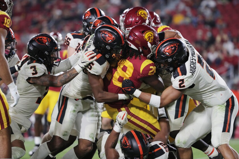 USC Trojans running back Keaontay Ingram (28) is surrounded by Oregon State players.