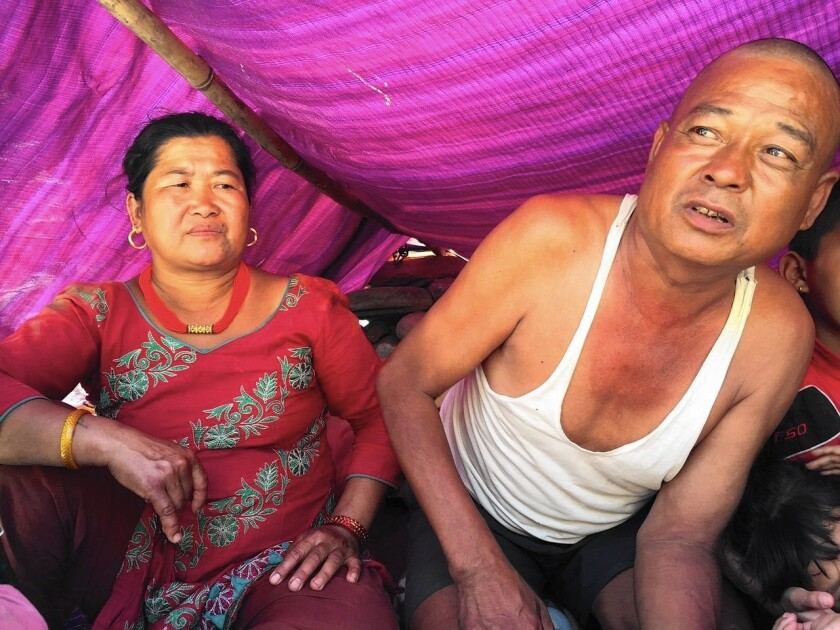 Nani Tamang, left, and husband Mangale live in a hut near where their village once stood in Jure, Nepal. A landslide wiped out the town in August, and the Tamangs are still awaiting aid from the government.