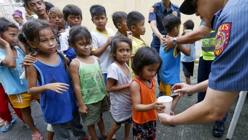 Manila police give out rice porridge to residents living along the coastal community of Baseco as th