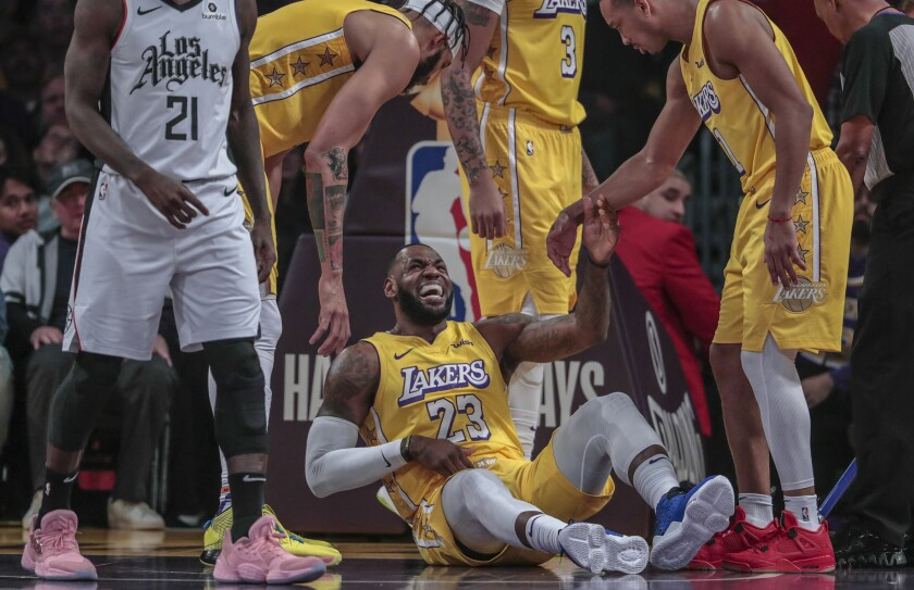 Lakers forward LeBron James grimaces in pain after colliding with Clippers guard Patrick Beverley on Dec. 25, 2019, at Staples Center.