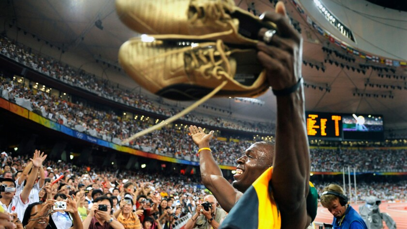 Usain Bolt celebrates after helping the Jamaican team win gold in the 400-meter relay at the 2008 Beijing Olympics.