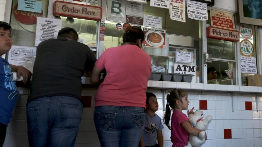 Osvaldo Orozco, 10, his father, also named Osvaldo Orozco, his mother Aida Villagrana, 30, his brother Daniel Orozco and sister Amy Orozco, all wait at the counter of Carnitas Michoacan.