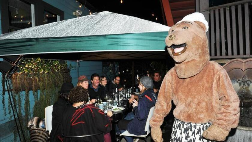 Bear greets guest during the Cow by Bear dinner party. (Rick Nocon)