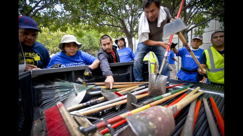Jornaleros del Centro de Empleo de Carecen recogen sus palas y otras herramientas en el jardín Evelyn Thurman Gratts, en Los Angeles.