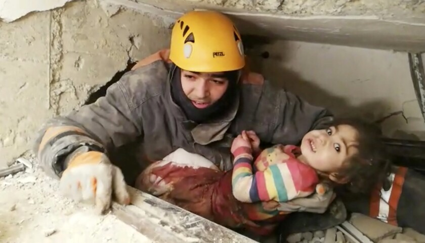 An image taken from video shows a rescuer pulling out a girl from the rubble of a collapsed building in Elazig, Turkey, on Saturday.