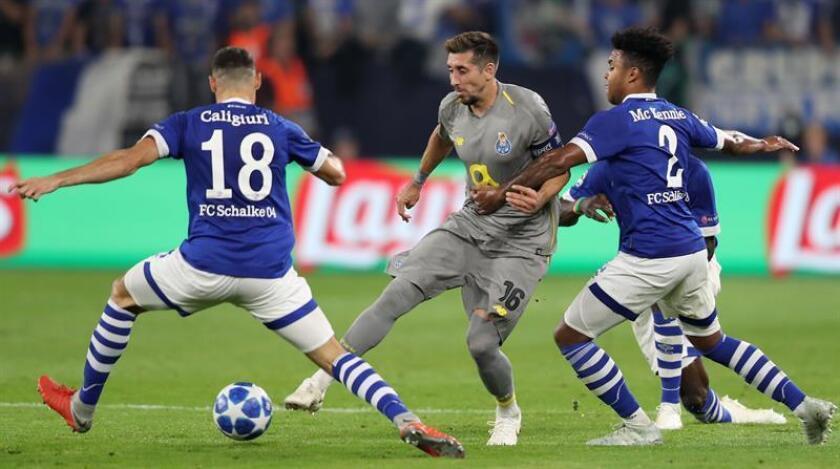 Hector Herrera (c) del Oporto pelea por el balón con Daniel Caligiuri (i) y Weston McKennie (d) del Schalke hoy, martes 18 de septiembre de 2018, durante un partido del Grupo D por la primera jornada de la Liga de Campeones de la UEFA, disputado entre el FC Schalke 04 y el FC Oporto, en Gelsenkirchen (Alemania). EFE