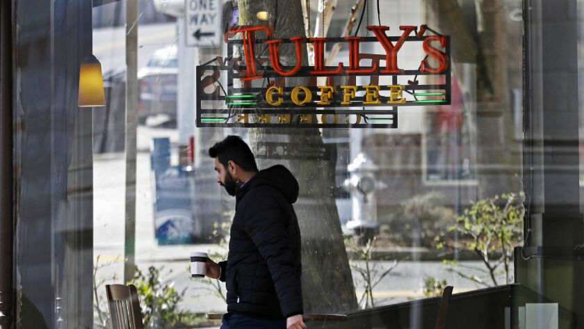 A man carries a cup as he walks past an open Tully's Coffee store, Friday, March 9, 2018, in Tacoma,