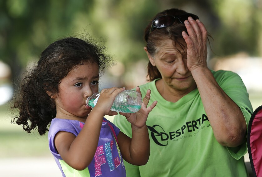 Lilly Santiago, 5, left, cools off with her mother, Lupita, 56, after playing basketball at Lanark Park on Thursday.