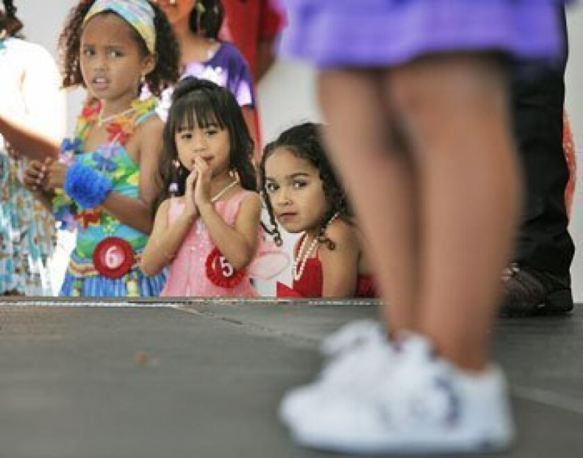Contestants in the Little Miss Fil-Am Pageant (from left) Eurice McNeal, 8; Jeanella Serquina, 4; and Zari Whitaker, 4; watched Belle Alicia Vazquez's talent routine. (John Gibbins / Union-Tribune)