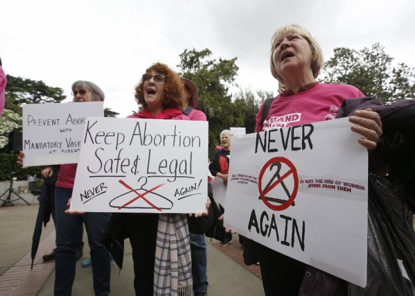 Kathy Holcomb, left, Sandra Jones, center, and Kathi Timmons gather a rally at the state Capitol in support of abortion rights, Tuesday, May 21, 2019, in Sacramento, Calif.