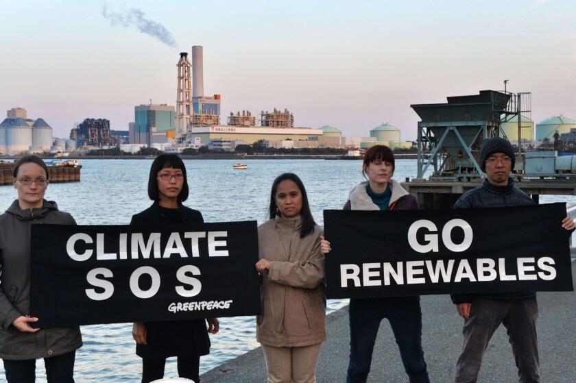 Members of environmental group Greenpeace display banners in Yokohama, suburban Tokyo to protest against global warming.