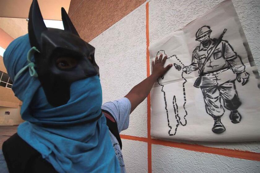 Un manifestante encapuchado protesta hoy, viernes 12 de enero de 2018, en Chilpancingo, estado de Guerrero (México). EFE
