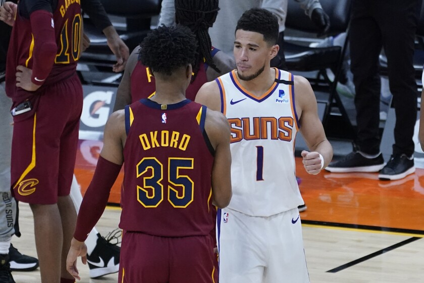 Phoenix Suns guard Devin Booker (1) greets Cleveland Cavaliers guard Isaac Okoro (35) after an NBA basketball game, Monday, Feb. 8, 2021, in Phoenix. (AP Photo/Matt York)