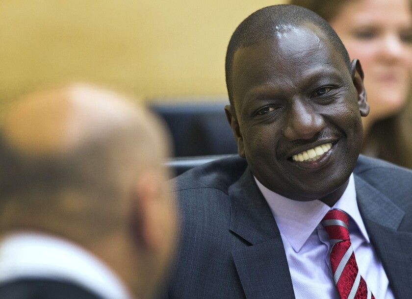 Kenyan Deputy President William Ruto speaks with his defense counsel before the start of his trial at the International Criminal Court in The Hague.