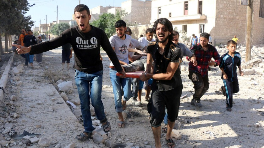 Syrians carry a stretcher as they evacuate victims from the rubble of a collapsed building after a reported U.S. airstrike in northern Syria on July 19.