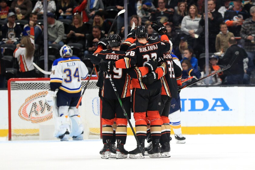 Ducks' Christian Djoos (29) and Jakob Silfverberg (33) congratulate Jani Hakanpaa (28) after he scored his first NHL goal during the second period at Honda Center on March 11.