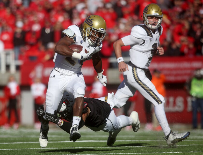 UCLA running back Paul Perkins tries to avoid the diving tackle attempt by Utah defensive end Jason Fanaika in the first half.