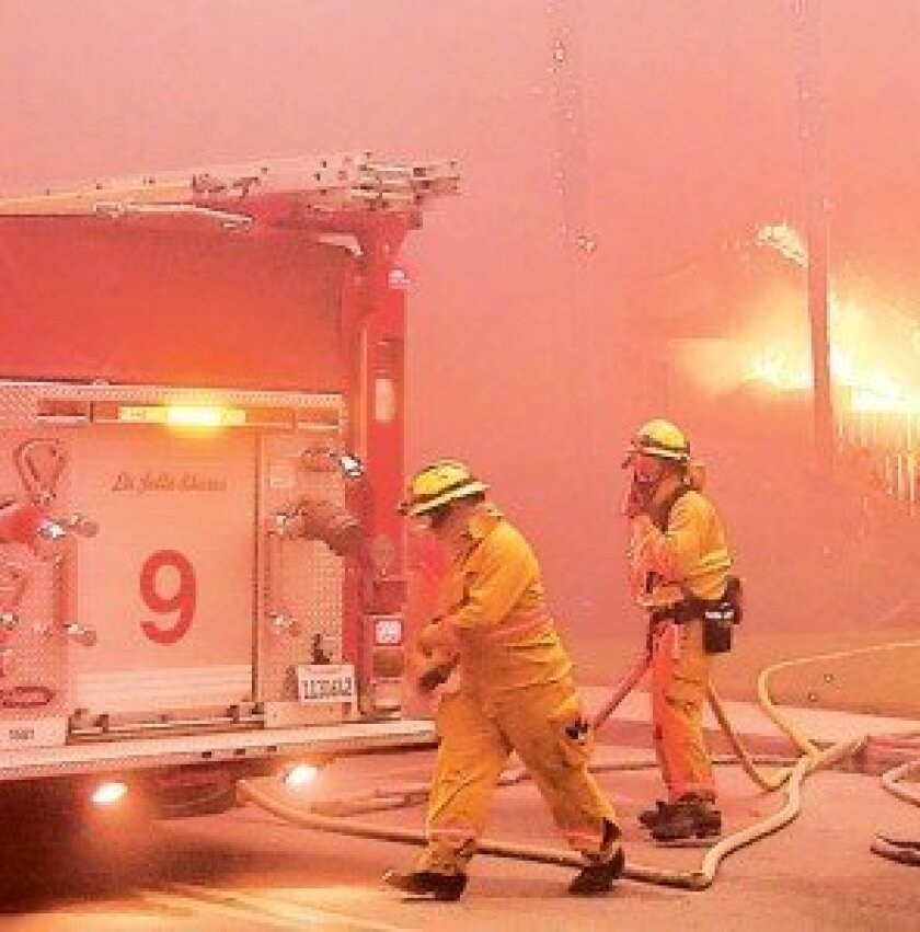 Firefighters work to protect homes in the Westwood area of Rancho Bernardo.