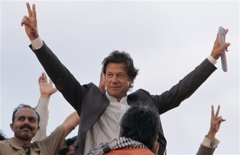 Pakistani cricket legend-turned politician Imran Khan waves to his supporters at a rally in Lahore, Pakistan on Saturday, March 23, 2013.  Khan rallied around 100,000 flag-waving supporters in the eastern city of Lahore on Saturday ahead of a historic national election later this spring. (AP Photo/