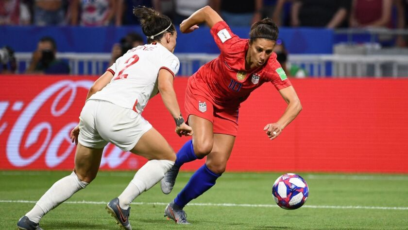 U.S. forward Carli Lloyd tries to maneuver around England defender Lucy Bronze during a Women's World Cup semifinal on Tuesday.