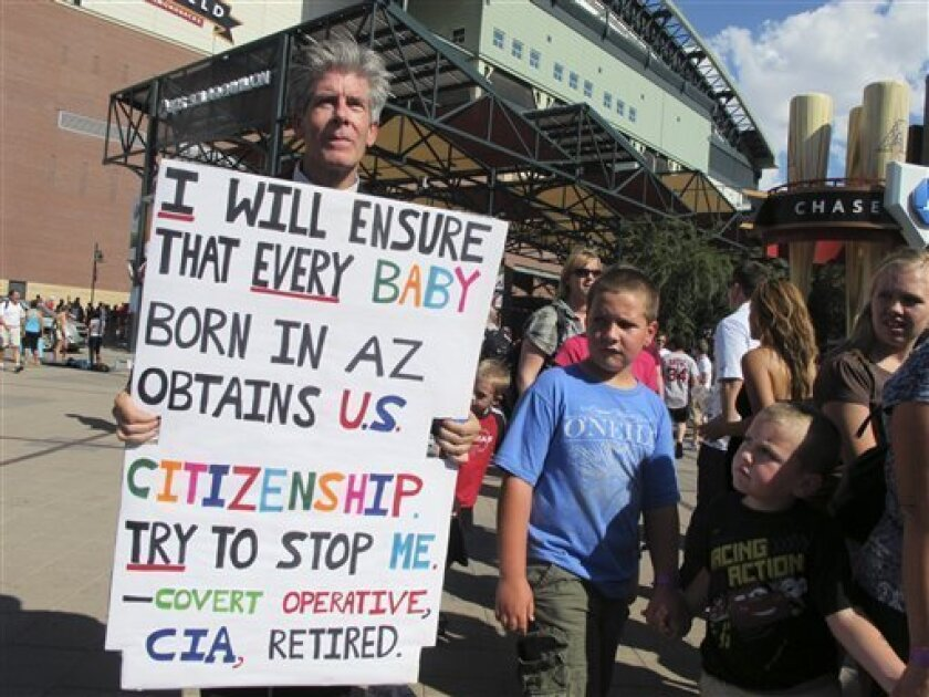 George Clifton holds a sign at a protest Tuesday July 12, 2011, outside the baseball All-Star Game in downtown Phoenix. Protesters voiced their opposition to a polarizing Arizona immigration law. (AP Photo/Amanda Lee Myers)