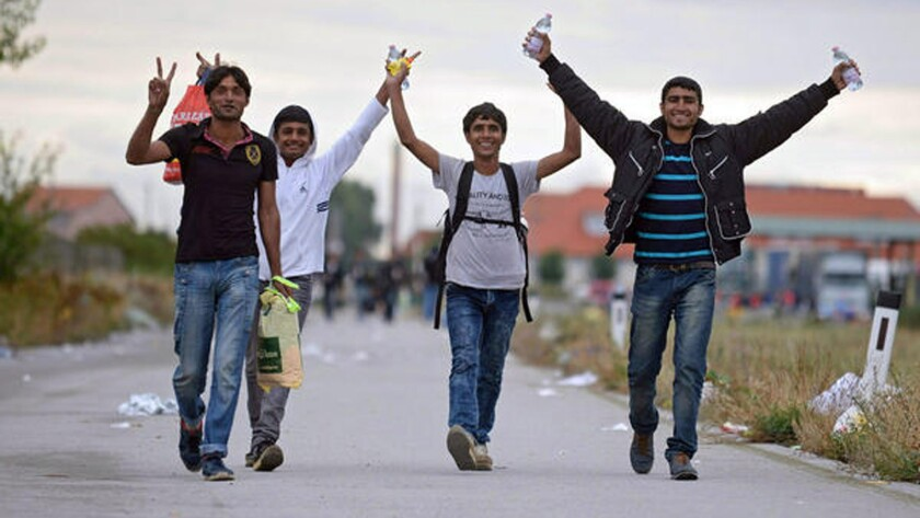 Refugees cheer as they cross the border from Hungary to Nickelsdorf, Austria, on Saturday.