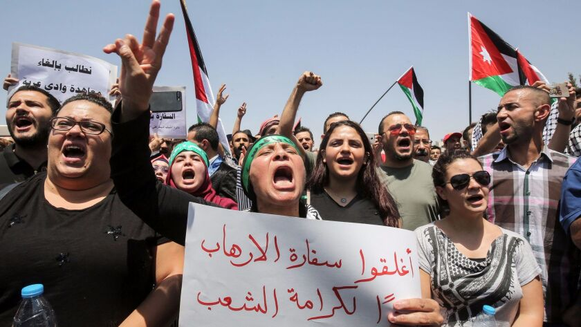A Jordanian protester flashes the victory gesture as she holds a sign calling for closing down the Israeli Embassy in the capital, Amman, on July 28, 2017.