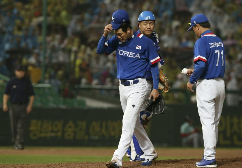 South Korea's starter Kim Kwang-hyun leaves the mound in the sixth inning after allowing three runs in the baseball gold medal game against Taiwan at the 17th Asian Games Sunday, Sept. 28, 2014 in Incheon, South Korea. Others are catcher Kang Min-ho and coach Cho Kye-hyun (71). (AP Photo/Eugene Hos