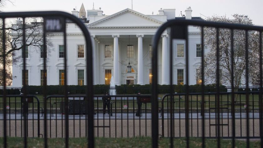 In this March 24, 2019 photo, The White House is seen behind security barriers in Washington. A Whit