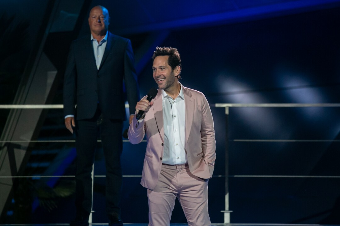 Paul Rudd smiles on stage and speaks into a microphone.