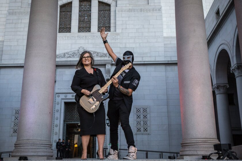 Councilwoman Monica Rodriguez strums the guitar of one of the event's performers in 2018.