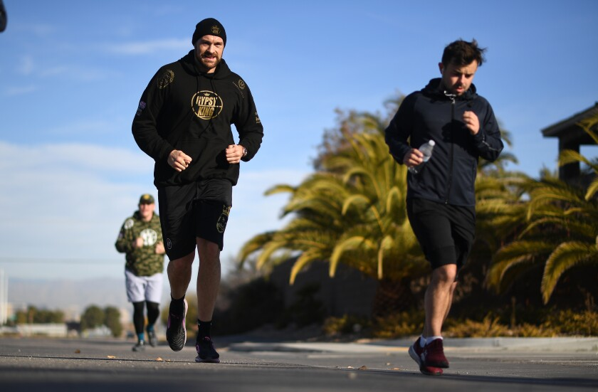 Tyson Fury, left, jogs with his trainers during a morning workout in Las Vegas.
