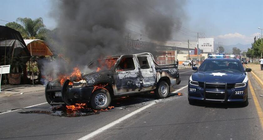 Una patrulla de la policía pasa junto a una camioneta en llamas en Uruapan (México). EFE/Archivo