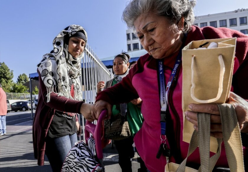 Nishat Brinta, left, distributes Christmas gifts at a weekly food bank set up by the Islamic Center of Southern California in Los Angeles.