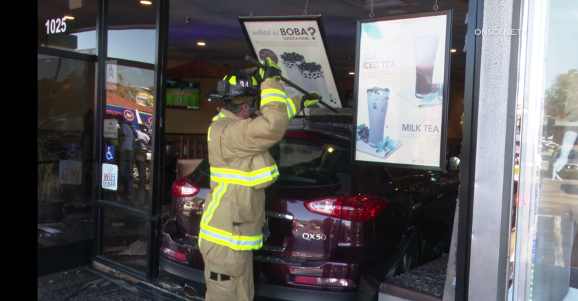 A firefighter sweeps glass from the top of a car that had smashed through a plate glass window at the front of Pho 7 Cow restaurant in National City on Tuesday afternoon.