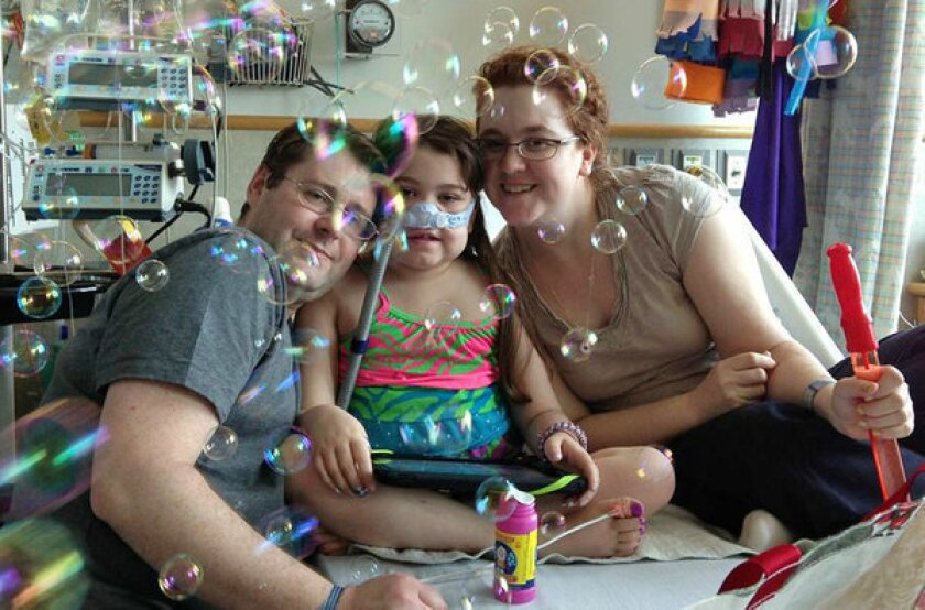 Sarah Murnaghan, center, marks the 100th day of her stay in Children's Hospital of Philadelphia with her father, Fran, left, and mother, Janet.